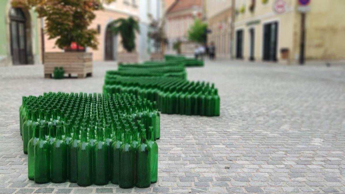 Exposición artística con botellas de vino